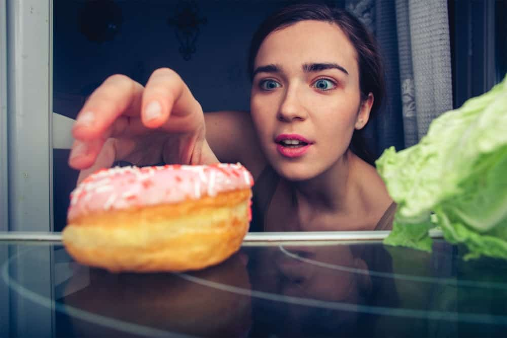Woman reaching for donut